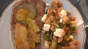 Zucchini-Chutney auf Grillfleisch neben Sommersalat
